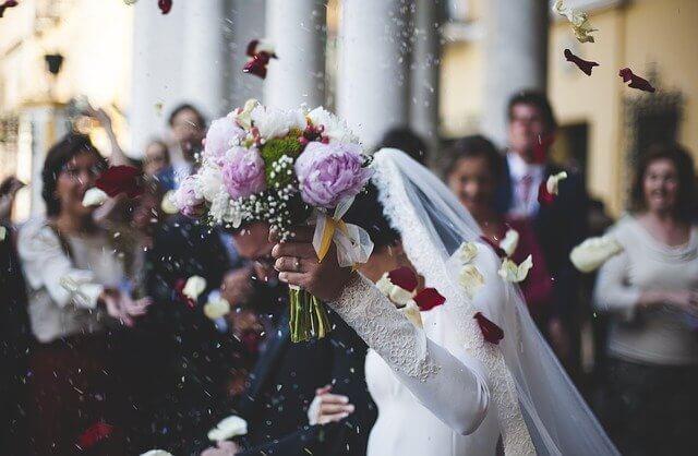 Brautpaar hält nach Vermählung gemeinsam einen Blumenstrauß