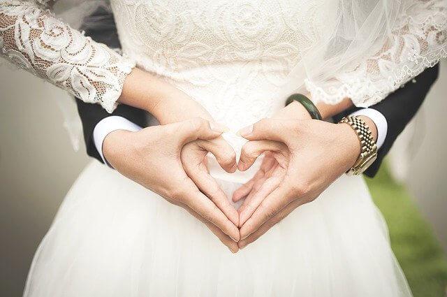 Brautpaar zeigt mit den Händen ein Herz