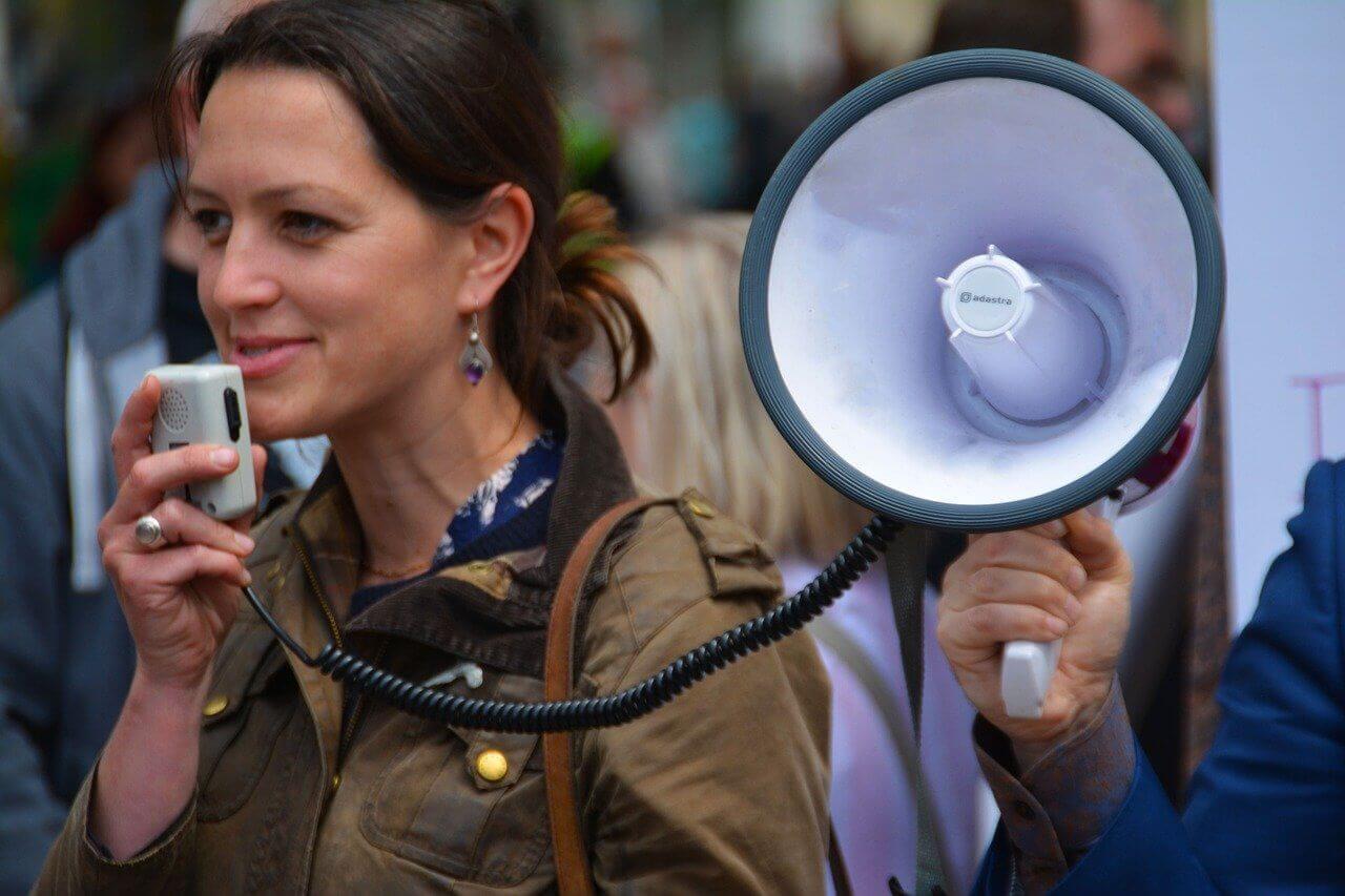 Frau mit Megaphon macht Wahlwerbung für Ihre Partei