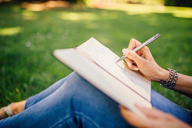Frau schreibt im Park auf Papier