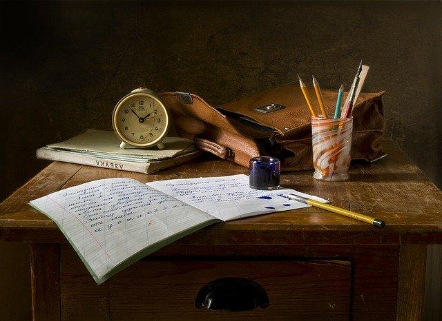Schreibtisch mit Schreibheft und vielen Stiften